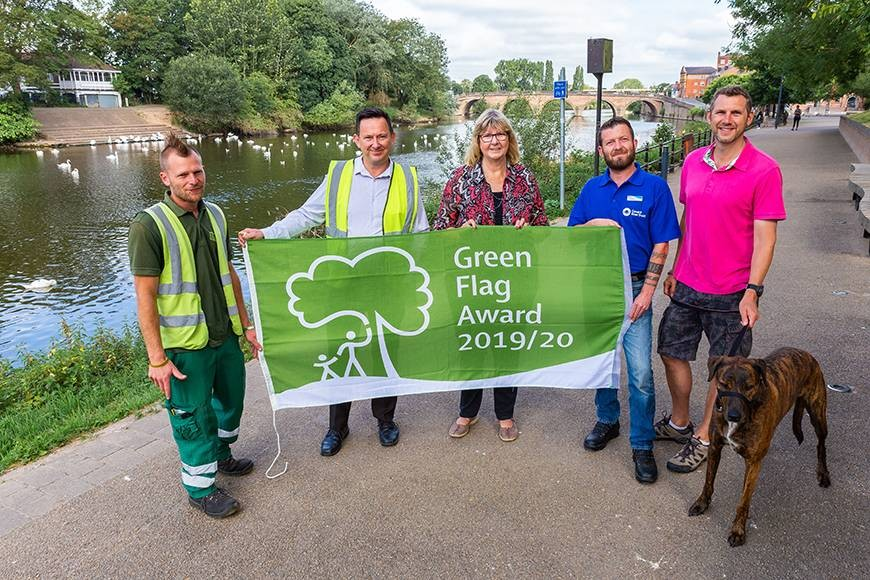 Celebrating the Green Flag award for Worcester's Riverside Park are Graham Pratt, Worcester City Council Riverside Team; Mark Worrall, Green Space Team Supervisor; Cllr Joy Squires; Timothy Booker, Canal and River Trust Area Operations Manager; Cllr Andy Stafford; and Dexx the dog.